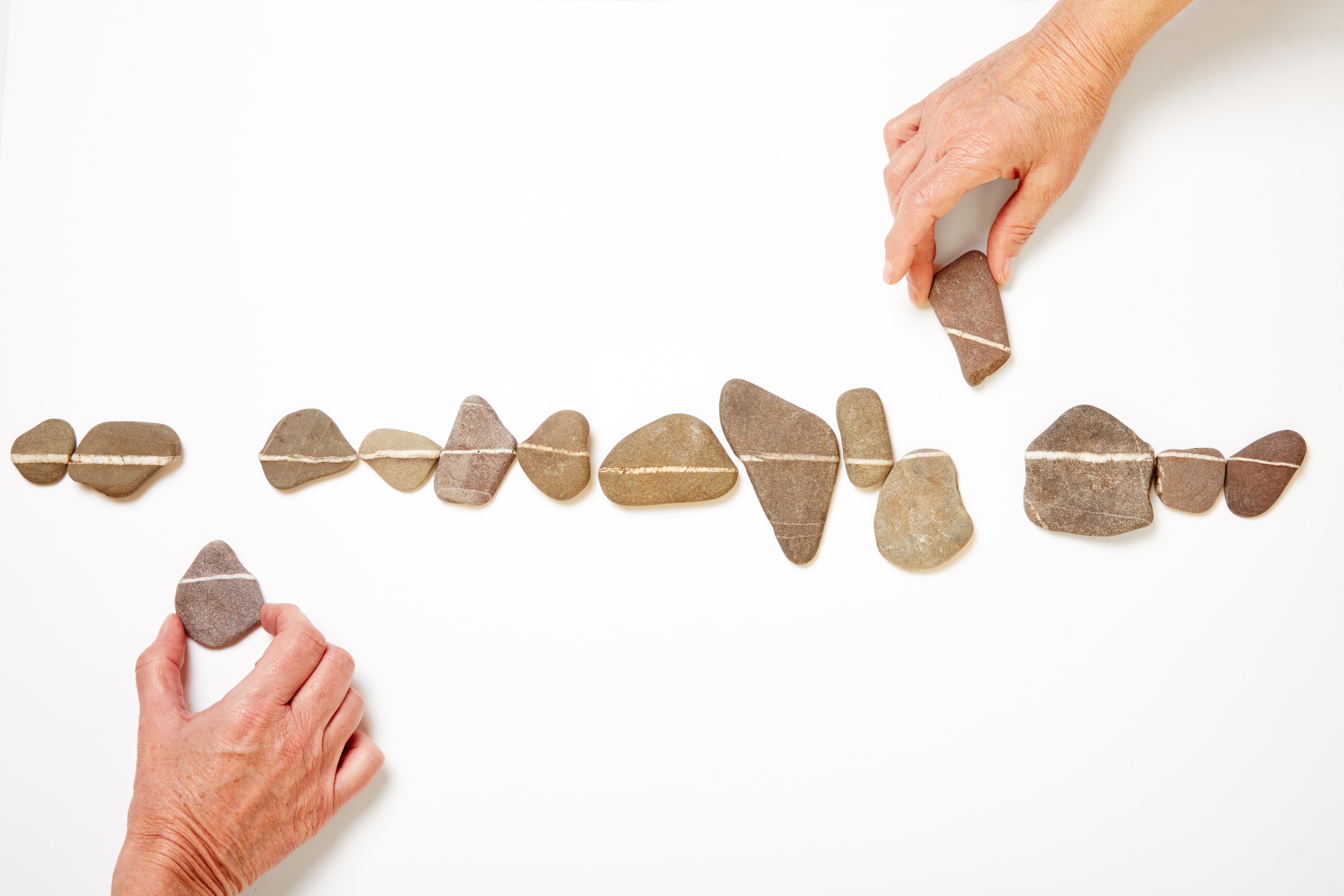 Zwei Hände bilden zusammen eine Linie aus vielen kleinen Steinen